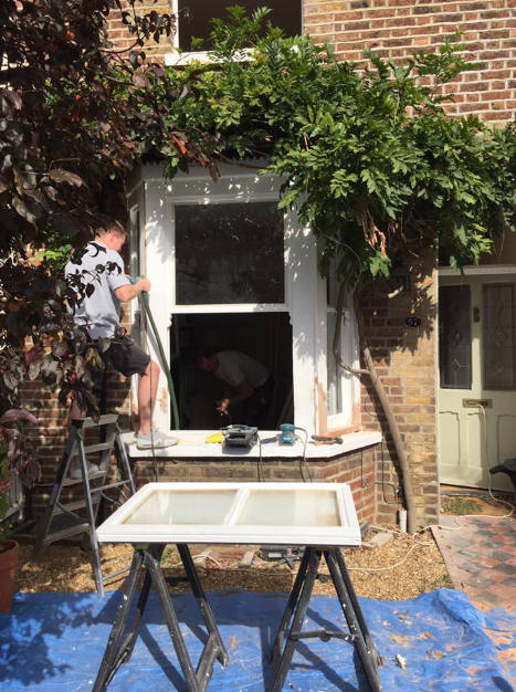 Draught proofing windows in Reigate men working